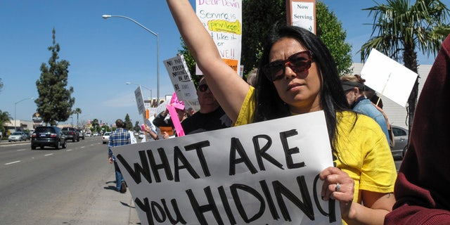 Protesters held signs as Rep. Devin Nunes visited Fresno, Calif., in March 2017.