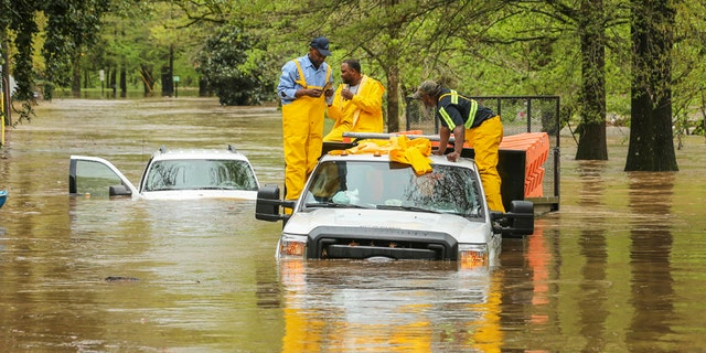 Men stand on a City of Atlanta vehicle submerged in flood water from a powerful storm in Atlanta, Wednesday, April 5, 2017. Severe storms raking the Southeast unleashed one large tornado and more than a half dozen apparent twisters Wednesday, toppling trees, roughing up South Carolina's 'peach capital' and raining out golfers warming up for the Masters. (John Spink/Atlanta Journal-Constitution via AP)