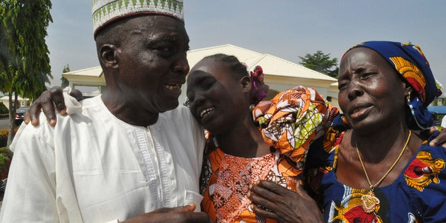 Family members celebrate as they embrace a relative, one of the released kidnapped schoolgirls, in Abuja, Nigeria, Saturday, May 20, 2017. ?The 82 Nigerian schoolgirls recently released after more than three years in Boko Haram captivity reunited with their families for the first time Saturday, as anxious parents looked for signs of how deeply the extremists had changed their daughters' lives. (AP Photo/Olamikan Gbemiga)