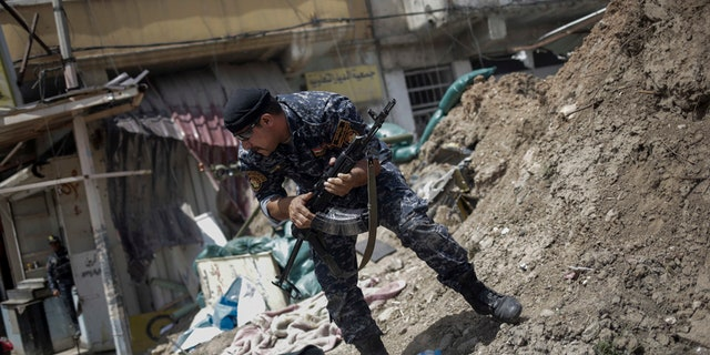 In this April 29, 2017 file photo, an Iraqi Federal Policeman runs away after he fired shots at an Islamic State group position on the western side of Mosul, Iraq.