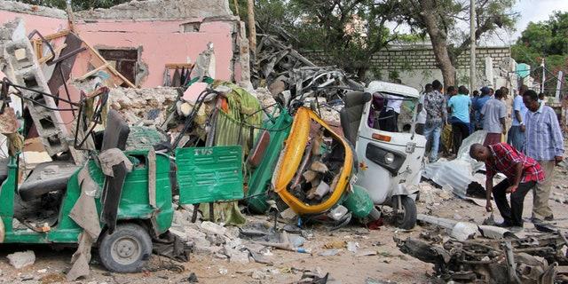 Somalis walk near destroyed vehicles at the scene of a car bomb blast and gun battle targeting a restaurant in Mogadishu, Somalia Thursday, June 15, 2017.