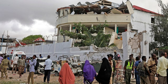 Somalis gather outside a destroyed building near a restaurant that was the scene of a car bomb blast and gun battle in Mogadishu, Somalia Thursday, June 15, 2017.