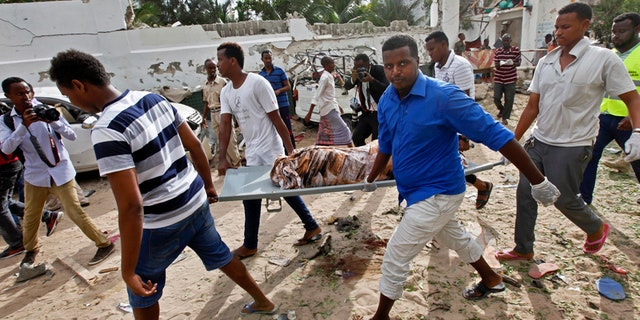 Somali men carry away the body of a civilian who was killed in a militant attack on a restaurant in Mogadishu, Somalia Thursday, June 15, 2017.
