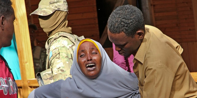 A mother whose daughter was shot in the head by attackers during a militant attack on a restaurant, grieves in Mogadishu, Somalia Thursday, June 15, 2017.