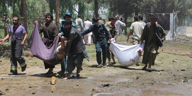Afghans carry the bodies of men at after a suicide car bombing in Helmand province southern of Kabul, Afghanistan, Thursday, June 22, 2017. The bomber struck outside a bank, targeting Afghan troops and government employees waiting to collect their salaries ahead of a major Muslim holiday and killing at least two dozen people, officials said. (AP Photo/Abdul Khaliq)