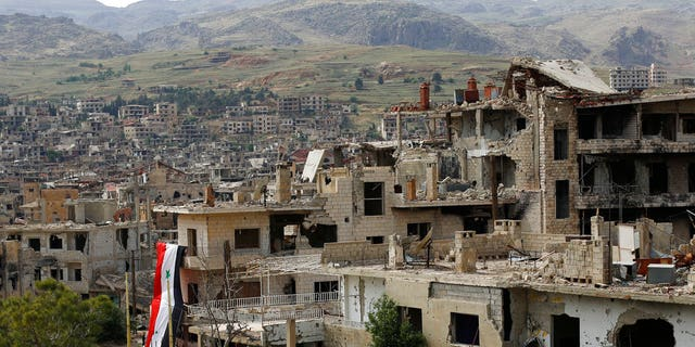 In this May 18, 2017 file photo, a Syrian National flag hangs out of a damaged building at the mountain resort town of Zabadani in the Damascus countryside, Syria.