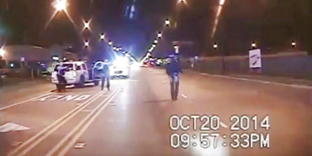 In this Oct. 20, 2014 file image taken from dash-cam video provided by the Chicago Police Department, Laquan McDonald, right, walks down the street moments before being fatally shot by Chicago Police officer Jason Van Dyke in Chicago.