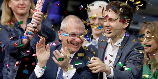 Green Party's gay rights activist Volker Beck, center, and fellow faction members celebrate with a confetti popper after German Federal Parliament, Bundestag, voted to legalize same-sex marriage in Berlin, Germany, Friday, June 30, 2017. (AP Photo/Michael Sohn)