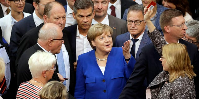 """German Chancellor Angela Merkel, center, gestures as a lawmaker raising a """"No""""-polling card during a meeting of the German Federal Parliament, Bundestag, at the Reichstag building on same-sex marriage in Berlin, Germany, Friday, June 30, 2017. (AP Photo/Michael Sohn)"""