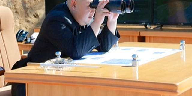 Kim Jung Un, center, using binoculars to watch the launch of a Hwasong-14 intercontinental ballistic missile, ICBM, in North Korea's northwest.