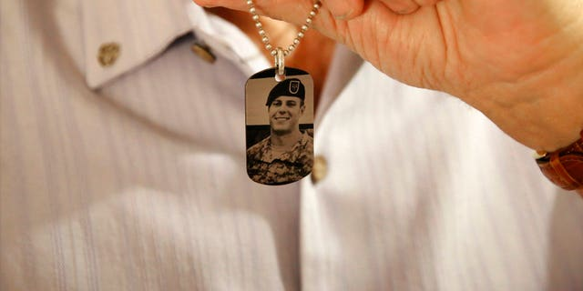 June 17: Brian McEnroe displays a memorial dog tag depicting his fallen son.