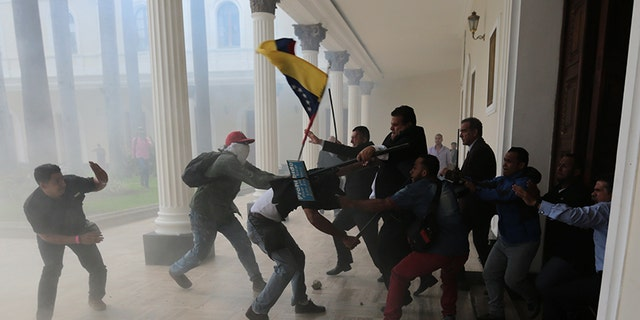 Opposition lawmakers brawl with pro-government militias who are trying to force their way into the National Assembly during a special session coinciding with Venezuela's independence day, in Caracas, Wednesday, July 5, 2017.
