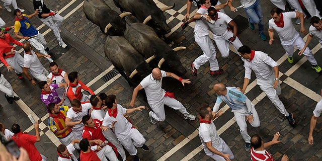 Revellers run in front of Jose Escolar fighting bulls during the second running of the bulls at the San Fermin Festival, in Pamplona, northern Spain, Saturday, July 8, 2017. Revellers from around the world flock to Pamplona every year to take part in the eight days of the running of the bulls. (AP Photo/Alvaro Barrientos)