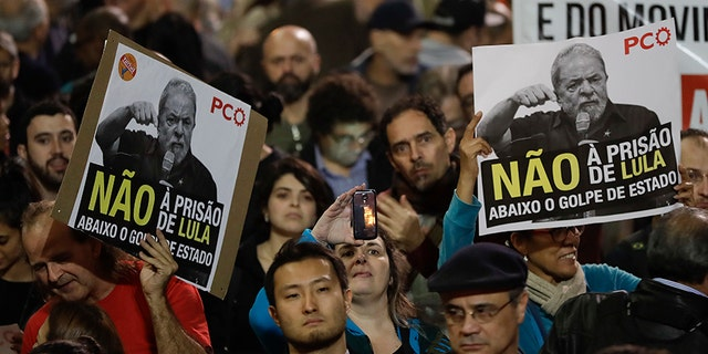 """Demonstrators hold signs that read in Portuguese """"No Prison for Lula,"""" during a protest against the decision by Judge Sergio Moro to convict former Brazilian President Luiz Inacio Lula da Silva in Sao Paulo, Brazil, Wednesday, July 12, 2017. Lula da Silva was found guilty of corruption and money laundering and sentenced to almost 10 years in prison. (AP Photo/Andre Penner)"""