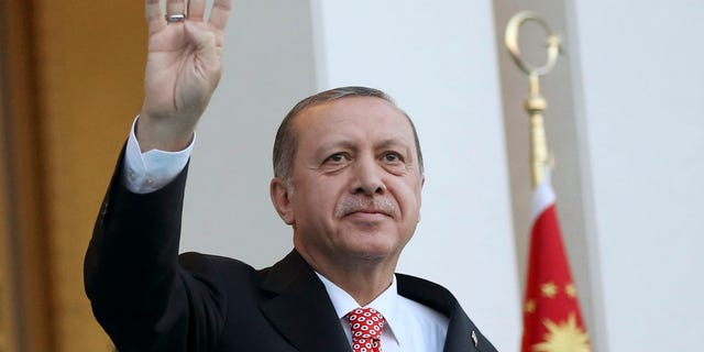 Turkey's President Recep Tayyip Erdogan waves to supporters outside the Presidential Palace.