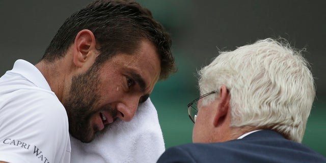 Croatia's Marin Cilic wipes his face as he has treatment on his foot as he takes a medical timeout during the Men's Singles final match against Switzerland's Roger Federer.