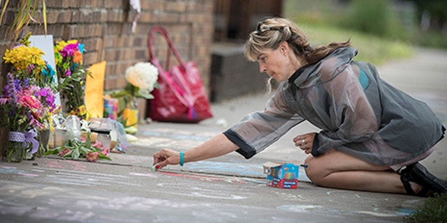 Megan O'Leary, of St. Paul, leaves a message on the sidewalk near the scene where a Minneapolis police officer shot and killed Justine Damond, of Australia, Monday, July 17, 2017, in Minneapolis.