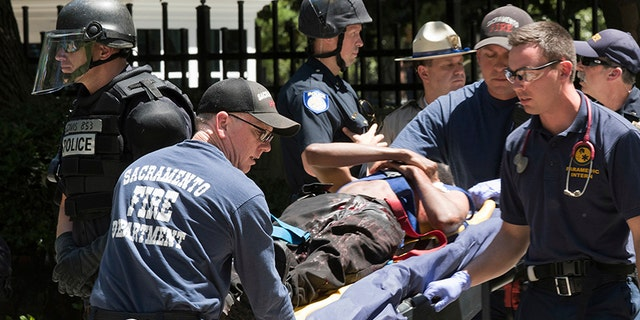 In this June 26, 2016, file photo, paramedics rush a stabbing victim to an ambulance after violence erupted during a white nationalist group's rally outside the state Capitol in Sacramento, Calif.