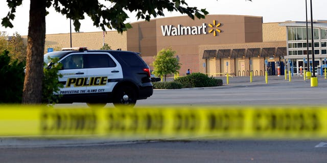 San Antonio police officers investigate the scene where eight people were found dead inside a tractor-trailer parked outside a Walmart.