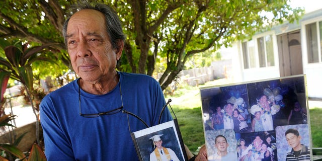 Clifford Kang, father of soldier Ikaika E. Kang, poses with photos of his son in Kailua this past July.