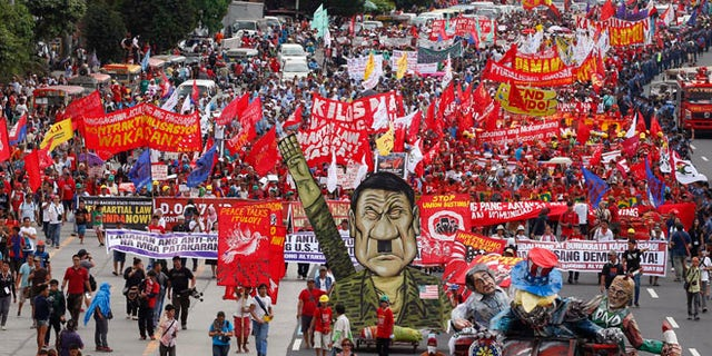Thousands of protesters march towards the Lower House with an effigy of President Rodrigo Duterte.