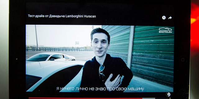 A tablet shows archive Youtube footage dated Monday, Aug. 2, 2015 featuring Yevgeny Nikulin after a Lamborghini Huracan race outside Moscow, Russia.