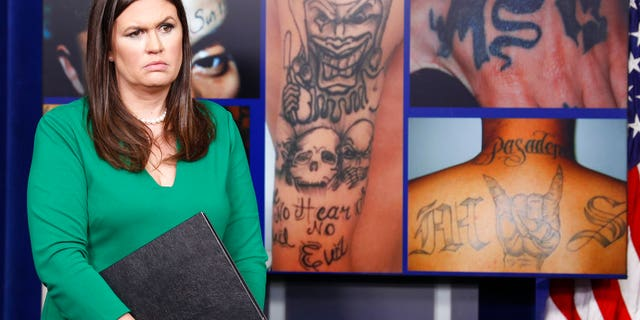 White House deputy press secretary Sarah Huckabee Sanders stands in front of pictures of MS-13 gang tattoos during a press briefing.