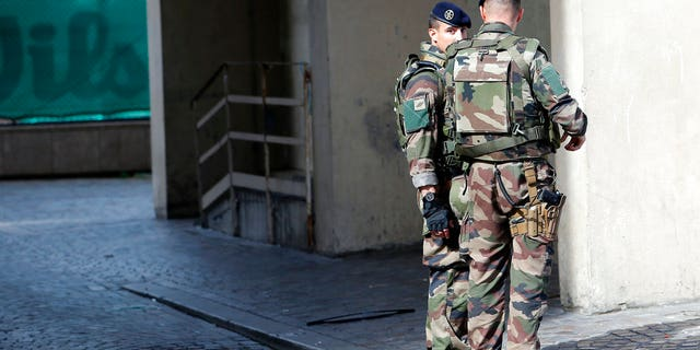 French soldiers stand near the scene of a Paris car attack.
