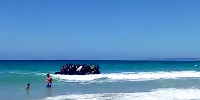 Beachgoers watched as around two dozen suspected migrants scattering on the beach in Cadiz, Spain.