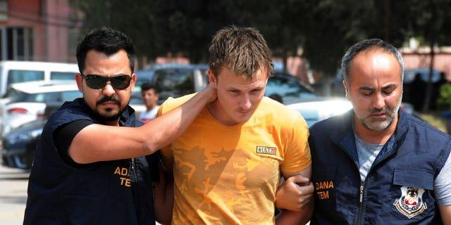 Turkish police walk with a handcuffed Renad Bakiev, center.