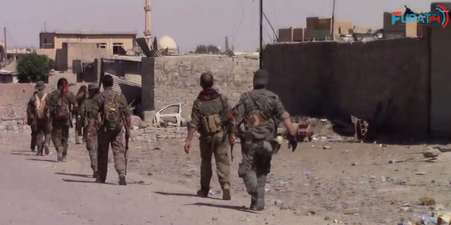 This frame grab from video released Friday, Aug. 11, 2017, and provided by Furat FM, a Syrian Kurdish activist-run media group, shows U.S.-backed Syrian Democratic Forces (SDF) fighters advance in Raqqa, Syria.