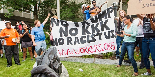 Protesters celebrate after toppling a statue of a Confederate solder in Durham, N.C. Monday, Aug. 14, 2017.