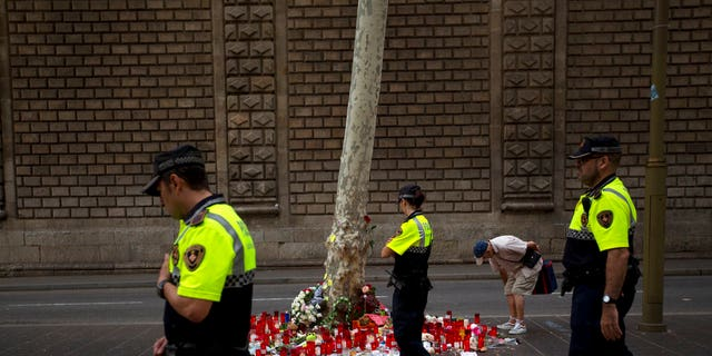 Police officers walk past candles and flowers placed on the ground after a terror attack that killed 14 people and wounded over 120 in Barcelona, Spain, Sunday, Aug. 20, 2017. (AP Photo/Emilio Morenatti)