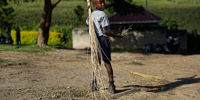 A boy sweeps outside the assembly hall during break at the Side-By-Side Boetheo School in Rakai, Uganda.