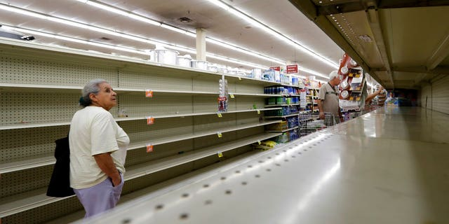 Shoppers pass empty shelves in a Houston grocery store as Hurricane Harvey intensifies.