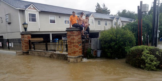 Residents sit on a fence surrounded by floodwaters in Houston, Texas.
