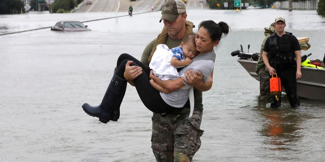Houston Police SWAT officer Daryl Hudeck carries Catherine Pham and her 13-month-old son Aiden after rescuing them from their home surrounded by floodwaters from Tropical Storm Harvey.