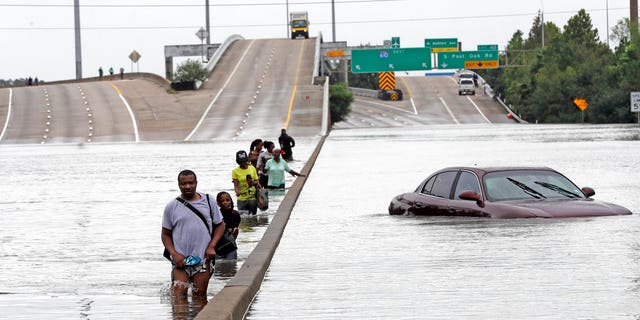 Evacuees on a flooded section of Interstate 610 in Houston, Texas.