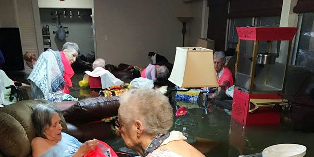 Residents of the La Vita Bella nursing home in Dickinson, Texas, sit in waist-deep flood waters caused by Hurricane Harvey. (Trudy Lampson via AP)