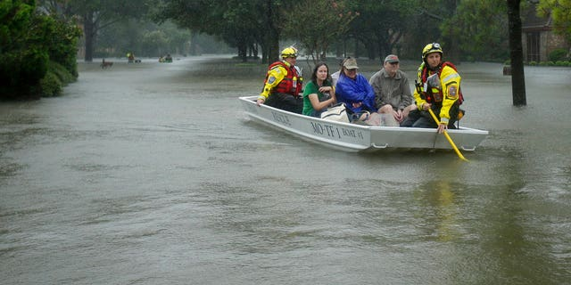 A FEMA rescue team evacuates people from a neighborhood inundated by floodwaters from Tropical Storm Harvey in Houston, Texas.