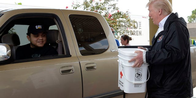 President Donald Trump helps load donated items for people impacted by Hurricane Harvey during a visit to First Church of Pearland in Pearland, Texas, Saturday, Sept. 2, 2017. (AP Photo/Susan Walsh)