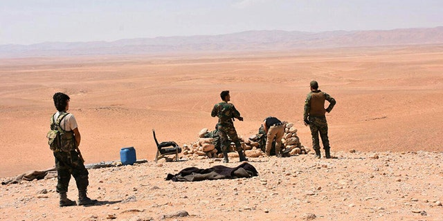 Syrian troops stand guard at one of the front line hills where they are fighting ISIS militants in the eastern city of Deir el-Zour, Syria.