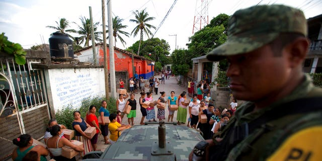 A soldier looks on as housewives stand in line for rations and water in Juchitan, Oaxaca state, Mexico, a zone heavily affected by Thursday's magnitude 8.1 earthquake, Saturday, Sept. 9, 2017.