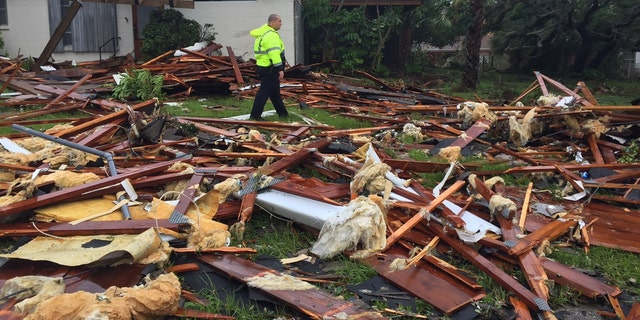 Palm Bay officer Dustin Terkoski walks over debris from a two-story home at Palm Point Subdivision in Brevard County, Fla., after a tornado touched down on Sunday, Sept. 10, 2017. (Red Huber/Orlando Sentinel via AP)