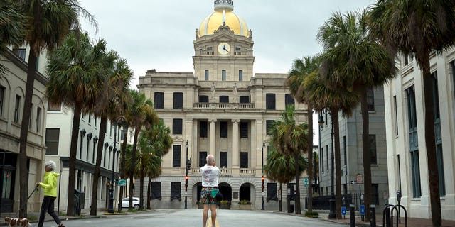 Savannah fine art photographer Dan Kaufman stops in the middle of nearly deserted downtown Savannah, Ga., Sunday, Sept., 10, 2017 to take a photo of City Hall before winds from the outer bands of Hurricane Irma are forecast to impact the area.