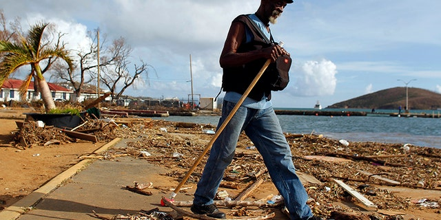 A man walks past debris caused by Hurricane Irma in Charlotte Amalie, St. Thomas, U.S. Virgin Islands, Sunday, Sept. 10, 2017.  The storm ravaged such lush resort islands as St. Martin, St. Barts, St. Thomas, Barbuda and Anguilla. (AP Photo/Ricardo Arduengo)
