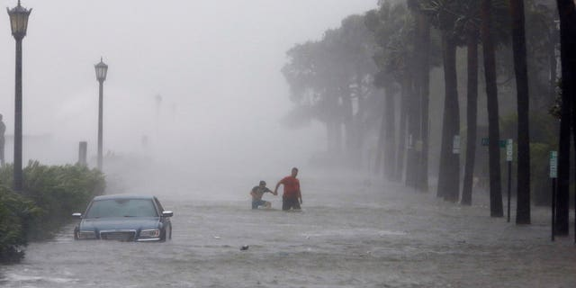 Pedestrians walk in a flooded street in Charleston on Monday, Sept. 11 during Tropical Storm Irma.
