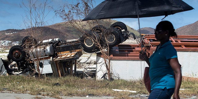 A woman passes an overturned truck after the passing of Hurricane Irma in St. Maarten.