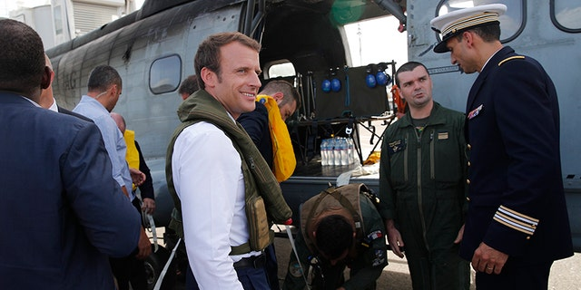 French President Emmanuel Macron waits on the tarmac of Pointe-a-Pitre airport.