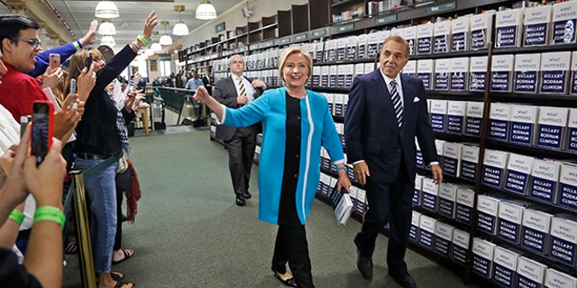 "Hillary Rodham Clinton, escorted by Leonard Riggio, chairman of Barnes and Noble, arrives to sign copies of her book ""What Happened"" at a book store in New York, Tuesday, Sept. 12, 2017. (AP Photo/Seth Wenig)"